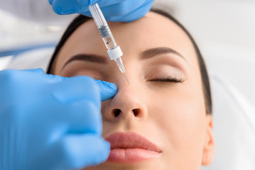 Serene female receiving collagen in nose