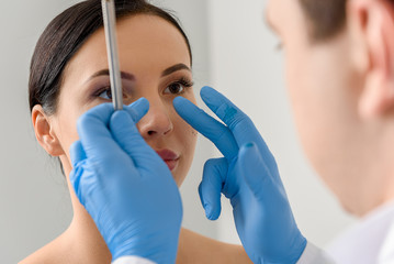 Physician examining face of serene female