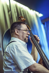 A European man, wearing glasses, plays the contrabass. Shoot from a low angle.