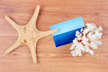 Top view of traveller's objects: photo card of the sea, sea star and coral
