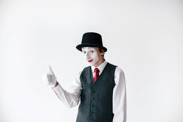 Mime in black hat and waistcoat holds his thumb up