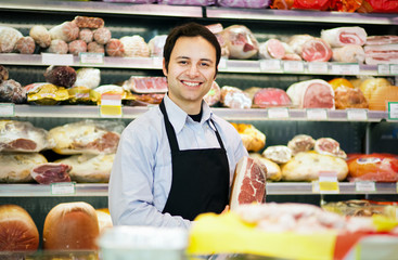 Smiling butcher in his grocery store