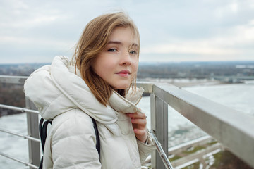Young adorable blonde teen girl having fun on the observation deck with a view of cloudy spring sky, frozen river, sunny windy weather