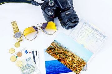 Top view. Objects of traveler isolated on white background: envelope, camera, cash, sunglasses, watch, photos of Italy, Carpathians and the sea and passport with visas