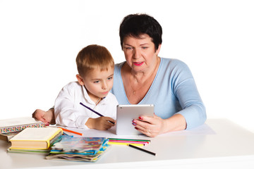 Grandmother with grandson learn and draw at table on a white background