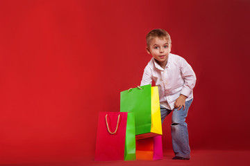 Little boy peers into packages with gifts on a red background