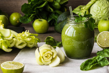 Detox diet. Green smoothie with different vegetables on wooden background