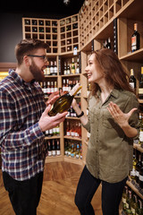 Vertical image of  Happy couple choosing bottle of wine