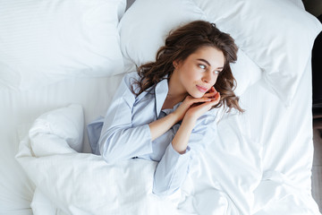 Young brunette woman wearing pajamas in bed at home