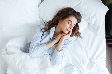 Top view of young beautiful woman in pajamas sleeping peacefully