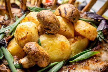 Grilled potatoes and mushrroms with meat and herbs close up