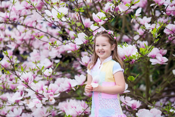 Wall Mural - Child with magnolia flower. Little girl with flowers