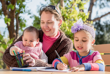 Mother And Little Daughters Drawing Pictures Together Outdoors In Spring