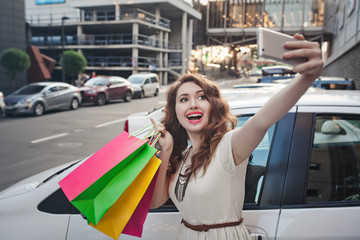 Beautiful young girl stands near a white car, makes a shopping, selfie
