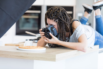 Girl lying on table and photographing cake