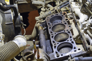 The cylinder block of the four-cylinder engine. Disassembled motor vehicle for repair. Parts in engine oil. Car engine repair in the service