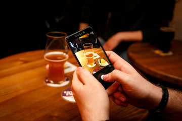 Smartphone in hands taking photo of Beer glass in bar