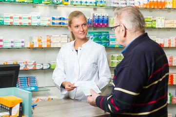 Junge Apothekerin bedient einen älteren Kunden