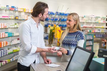 Junger Apotheker bedient eine Kundin