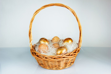 Easter golden eggs in a basket on table