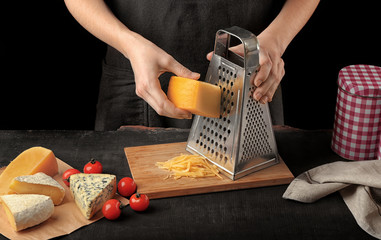 Woman grating cheese on kitchen table