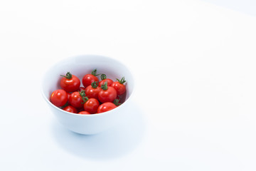 Cherry tomatoes harvested from home cultivation in a white bowl isolated on white background