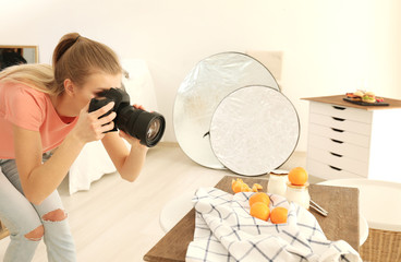 Young woman photographing food indoors