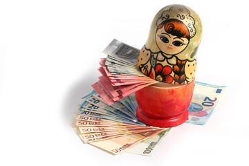 Russian national wooden toy stands on a pile of European paper bills euro