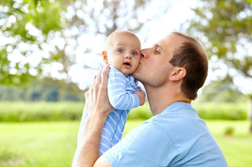Portrait of young father kissing his newborn son