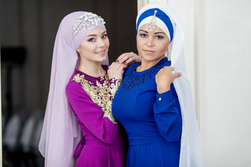 Two young beautiful muslim girls with makeup in pink and blue wedding dress with a beautiful white headdress
