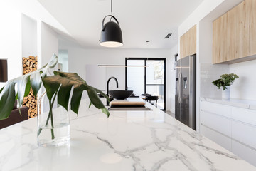 Kitchen marble bench close up with black hanging pendant and vase
