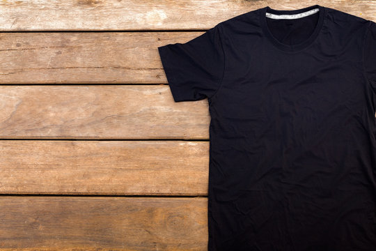 Black color t-shirt mock-up on wooden background. unfold single shirt round neck(O-neck)