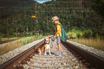 Little boy with dog stay on the railwai among forest