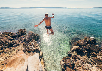 Man jumps in blue sea lagune water