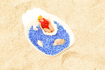 Handmade clay model on shell. Beach scene with artificial water and natural coral sand.