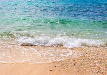 Turquoise sea water over white sand beach. Clean and relaxing sea wave splashes over seashore.