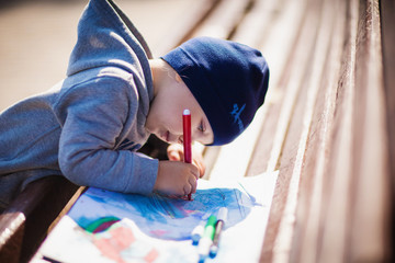 The child paints with felt-tip pens