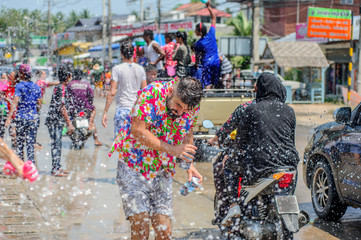 Thais and tourists shooting water guns, pour water on each other, having fun at Songkran festival, the traditional Thai New Year