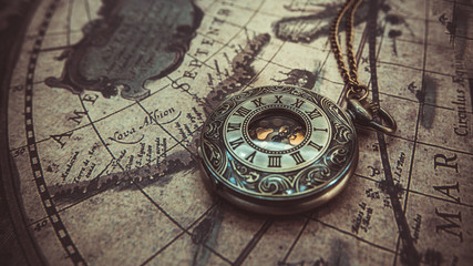 Antique necklace pendant watch on the ancient world map.