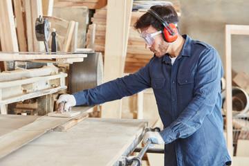 Schreiner schleift Holz an Bandschleifmaschine