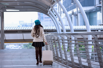 Asian Travel woman wearing sweater coat, blue yarn hat and hold smart tablet with luggage, walking on shopping business street background for traveler vacation tourist concept
