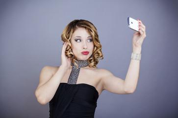 Jeune femme  en tenu de soirée, prend un selfie avec son téléphone portable