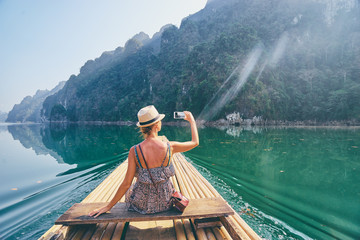 Travel and technology. Pretty young woman taking photo on smartphone sailing National Park lake on traditional boat.