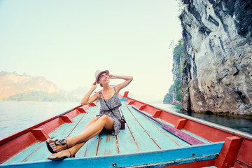 Happy vacation in Thailand. Pretty young woman taking sailing Khao Sok National Park lake on traditional longtail boat.