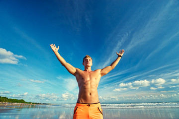 Victory and freedom. Young handsome strong man raising hands up on the beach against sky.