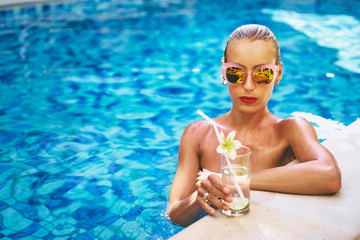 Enjoying vacation. Pretty young woman drinking cocktail in swimming pool.