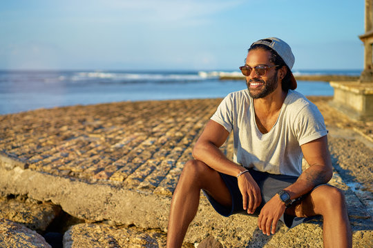Relaxed and cheerful. Outdoor portrait of happy young african man sitting near the sea.