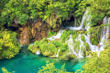 Plitvice Lakes National park, picturesque waterfall flows into the emerald lake surrounded by green summer forest, popular tourist destination in Croatia. Nature background for wallpaper or guide book