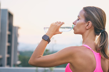 Healthy lifestyle and technology. Close up of young pretty woman drinking water with digital smart tracker outdoors.