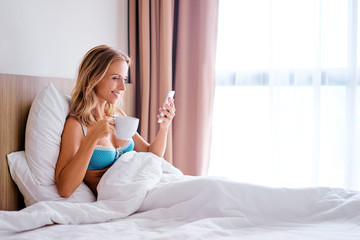 Morning with gadget. Overhead of beautiful young woman laying on the bed using smartphone.